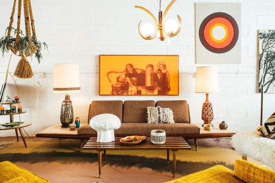 Adrian Pearsall sofa with built-in travertine end tables, $4,000, and custom mod art portraits created by Loren Weiner.