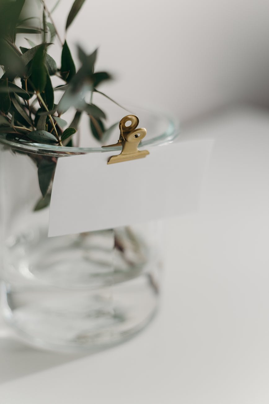 gold wedding band on clear glass vase