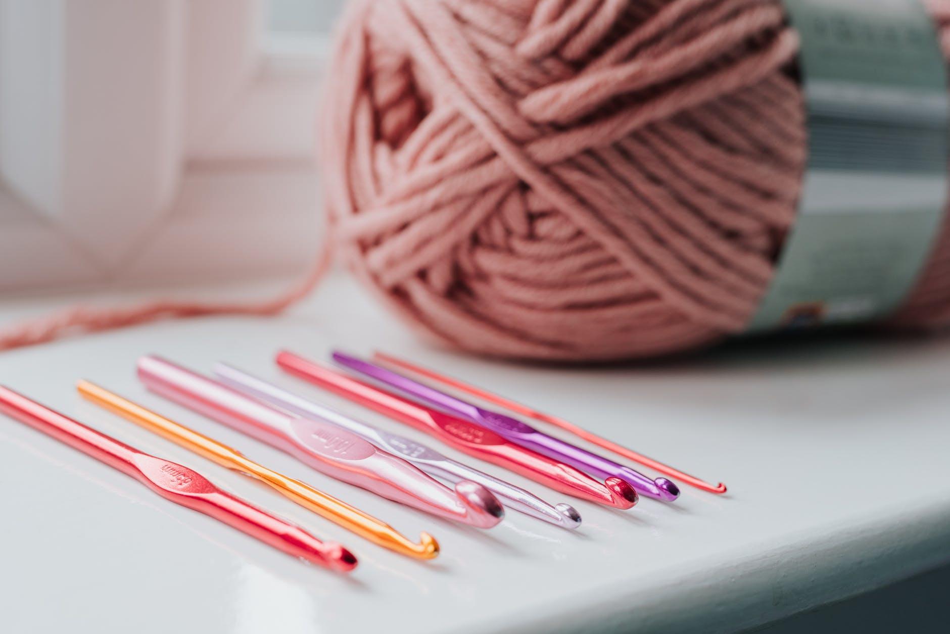 crochet needles and threads on windowsill
