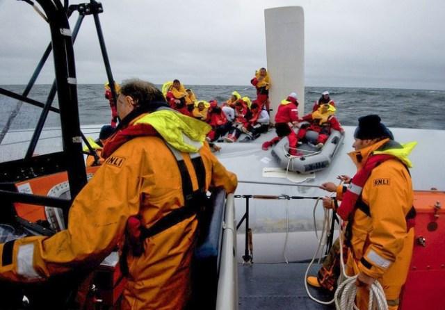 """Die irischen Retter bergen die einzelnen Crewmiglieder mit einem Gummiboot vom umgedrehten Rumpf der """"Rambler"""". © RNLI"""