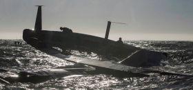 """Der 72 Fuß Kat """"USA 17"""" ist durchgekentert, die Flügel unter Ruder und Schwert zeigen unbrauchbar gen Himmel. © Guilain Grenier / Oracle Team USA"""