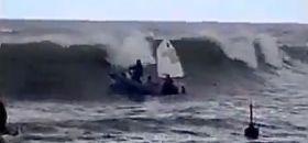 Der Trainer will den Opti durch die Brandung schleppen, als eine besonders große Welle anläuft.