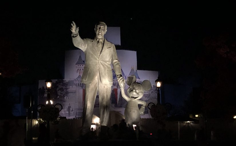 A statue of Walt Disney and Mickey Mouse in front of Sleeping Beauty castle at night.