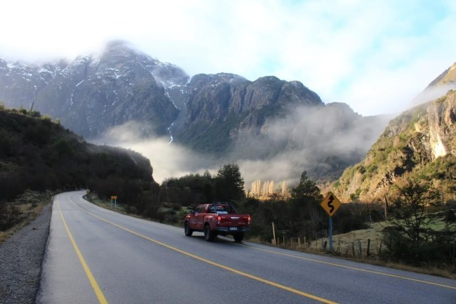 Caminhonete vermelha em uma estrada , ao fundo montanhas e árvores