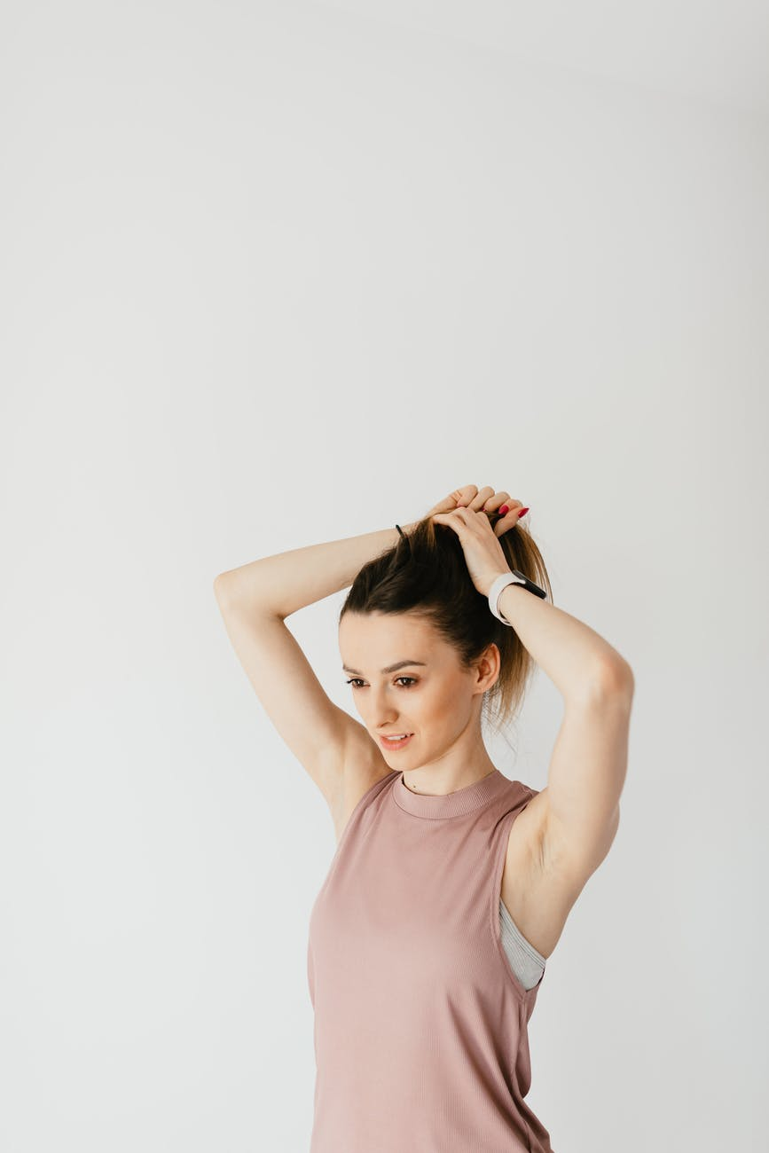 pensive young woman making ponytail in studio