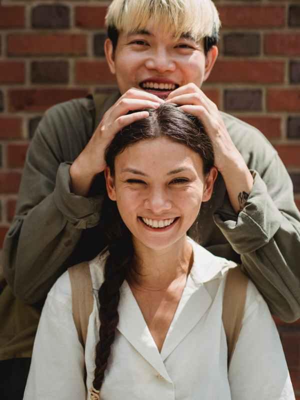 happy asian couple near brick wall