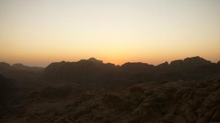 スモールぺトラの観光の帰りに、セルビスのドライバーに連れてきてもらった夕日の絶景ポイント。 オレンジ色の空と荒々しい岩山のシルエットがなんとも言えない光景だった