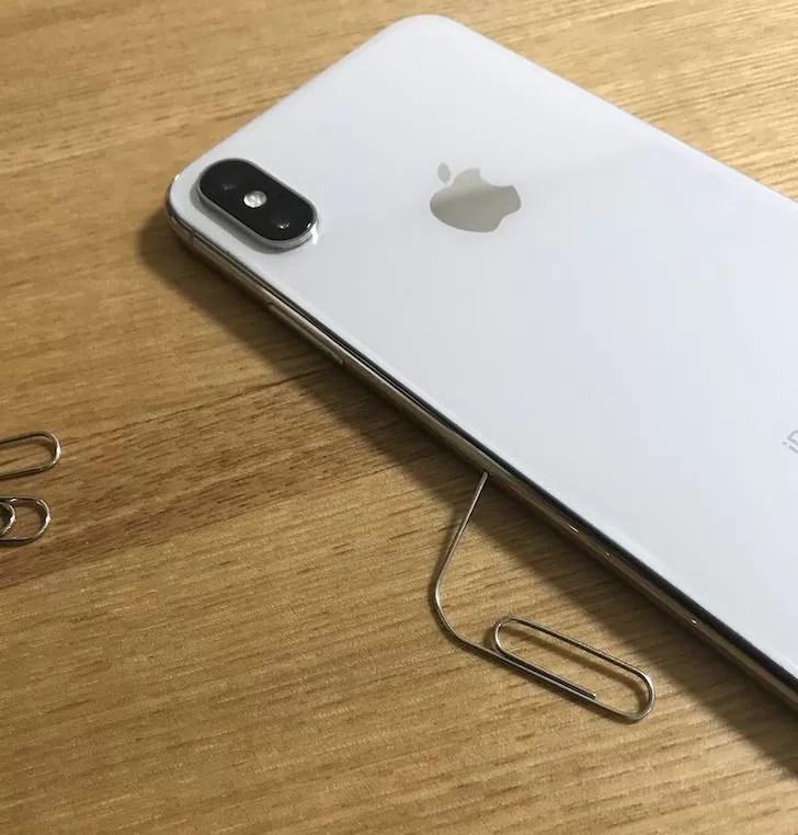 iPhoneにクリップを差し込んでSIMカードを取り出す