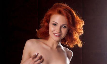 Een knappe roodharige vrouw, naakt tussen de lakens