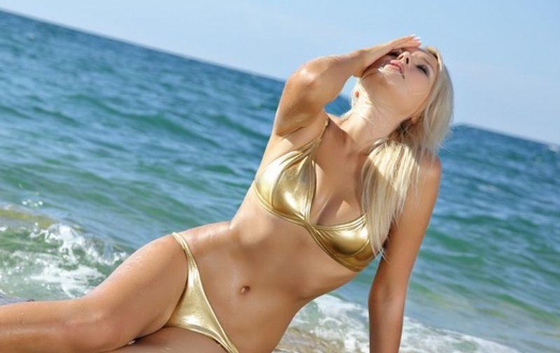 Blonde beach babe doet striptease op het strand