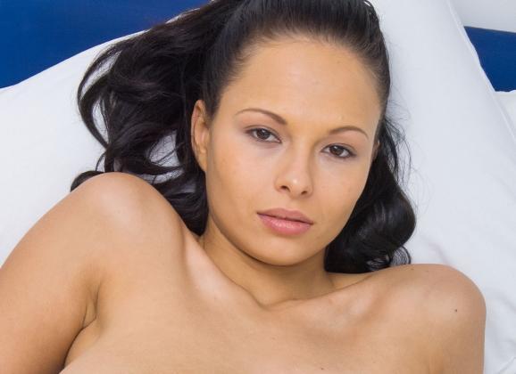 Domino, geile brunette met grote tieten, naakt op bed