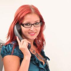 Een hete secretaresse met rood haar in sexy zwarte lingerie