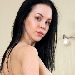 Kerija, donker haar en grote borsten, bloot op de eettafel
