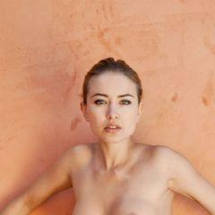 Lia May, sensuele schoonheid staat naakt tegen een muur