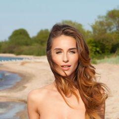 Rena, knappe brunette gaat naakt op het strand