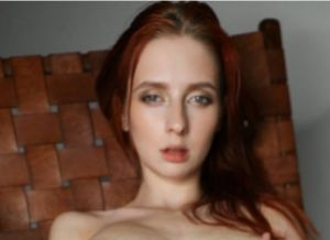 Helga Grey, naakt en wijdbeens in een stoel