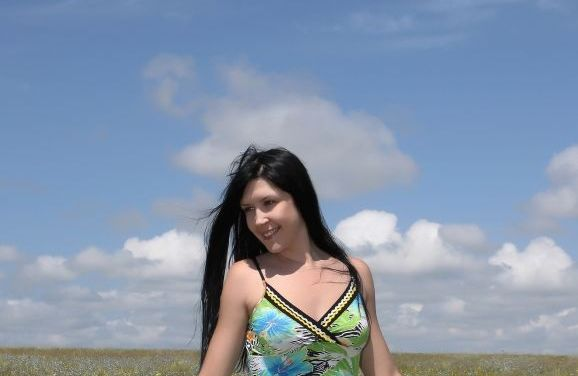 Karina G, naakt op een blauwe skippybal, op de hei
