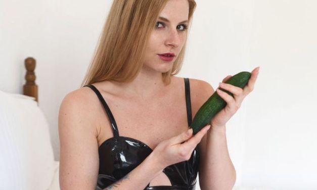 Jade, strak in het latex, pakt er een komkommer bij