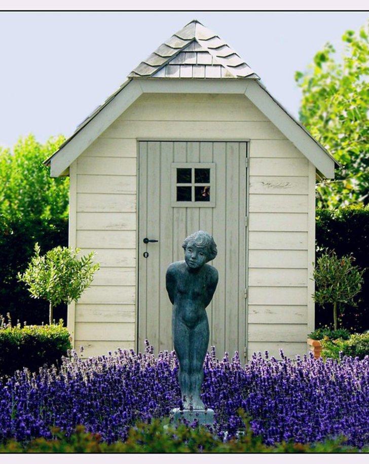 Eine Gartenstatue in einem Lavendelbeet vor ein schönen Gartenhütte