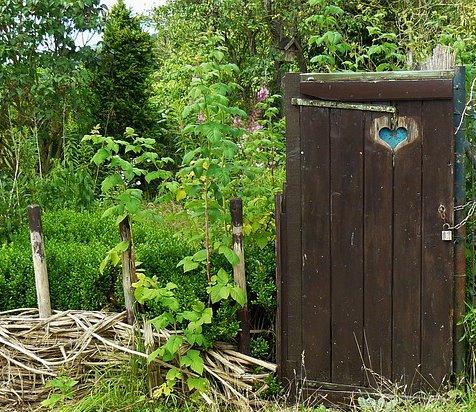 Die alte Tür eines Plumpsklos führt in einen verwilderten Bauerngarten