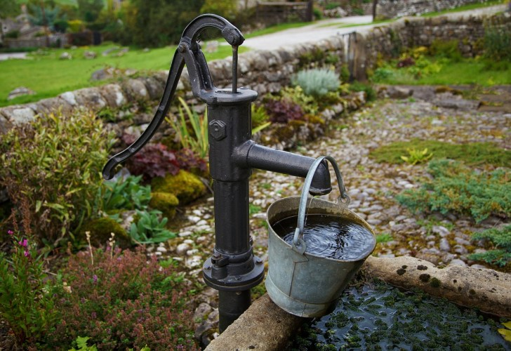 Schwengelpumpe an einem Gartenbrunnen