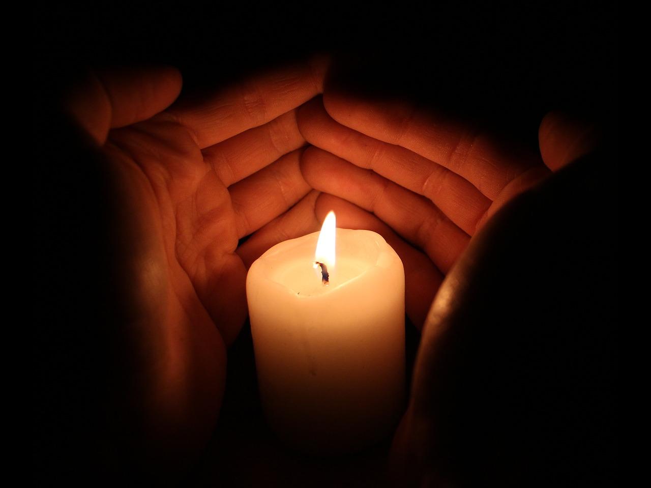 Brennende Kerze mit Händen