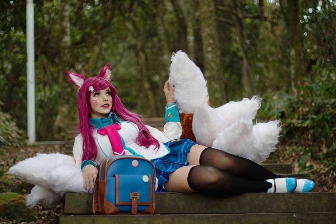 Foto da cosplayer brasileira Sayuki Lola com o cosplay da Ahri Colegial, de League of Legends. Ela está deitada em um banco em uma praça, perto da natureza.