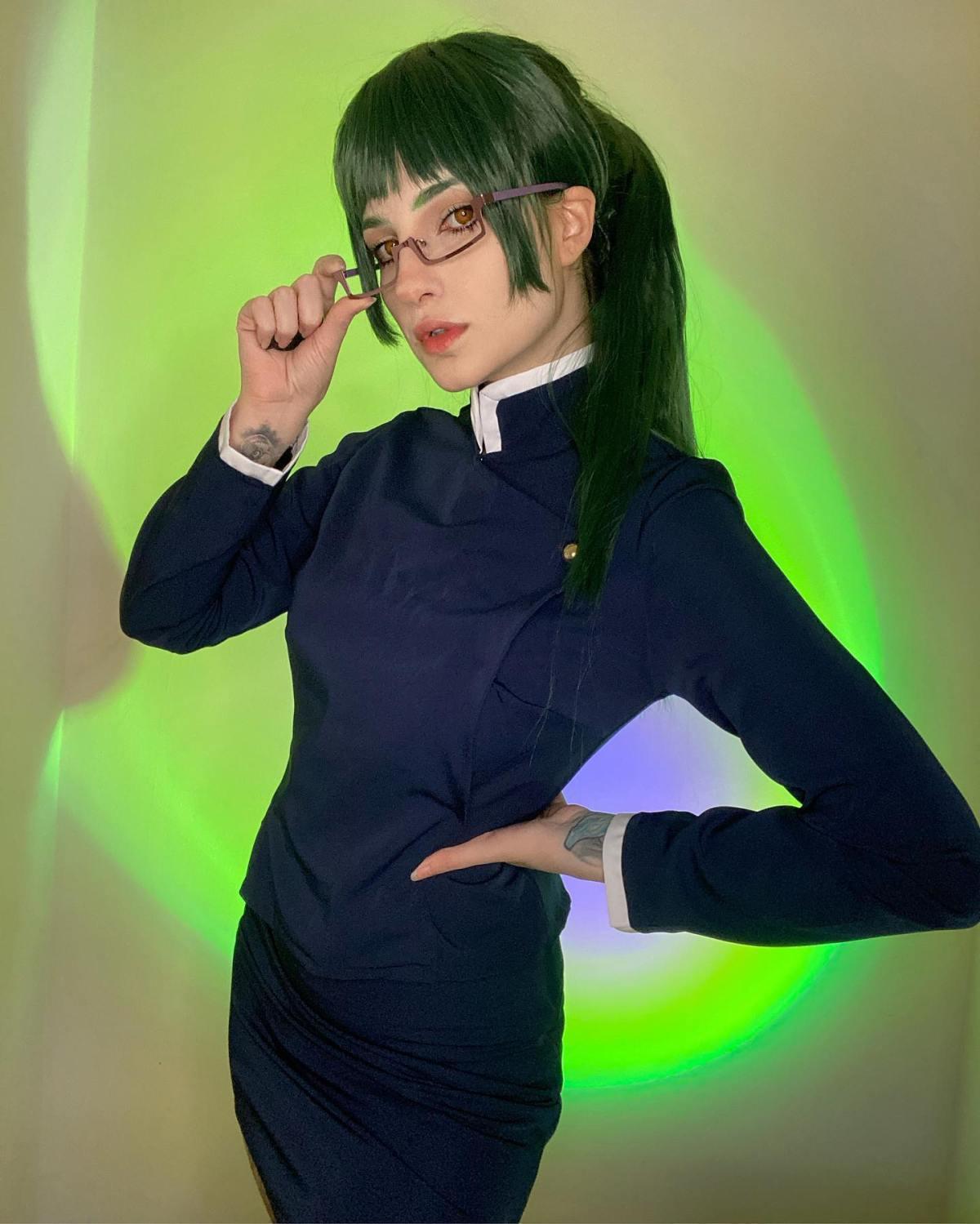 Cosplay da Maki Zenin, de Jujutsu Kaisen, da Samanta Bravin. O cosplay tem um vestido e a personagem tem cabelos verdes e óculos. A Samanta está olhando para a foto e uma das mãos está na cintura.