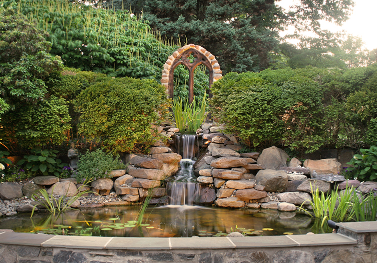 Outdoor stone fountain surrounded by lush landscaping