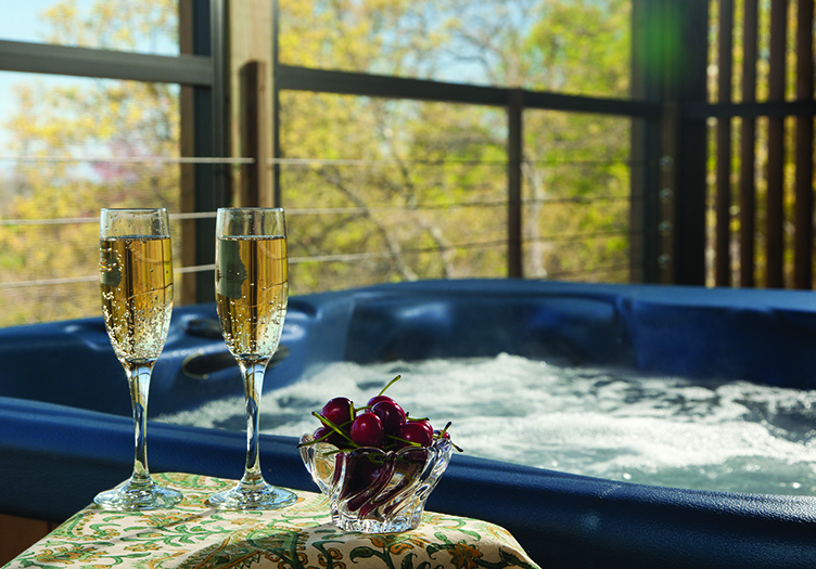 Two champagne flutes set next to a hot tub filled with warm bubbling water