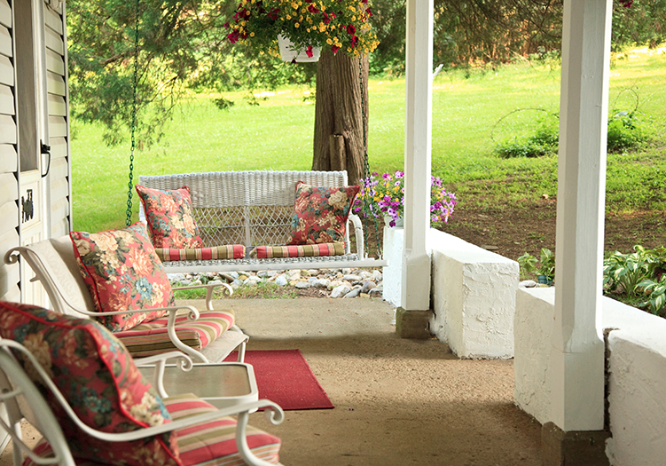 Charming Wi-Fi friendly Meadow Cottage Porch with swing and chairs and rose floral cushions