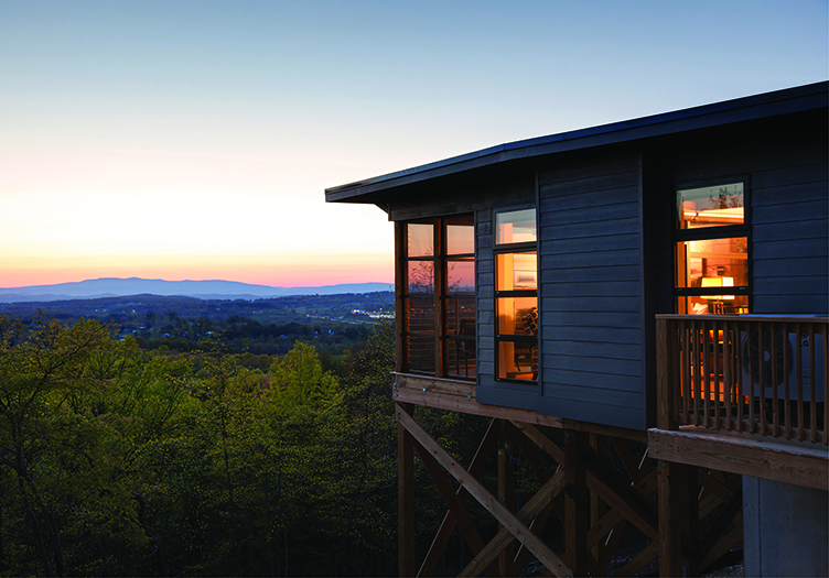 Exterior view of a warmly-lit cabin at sunset