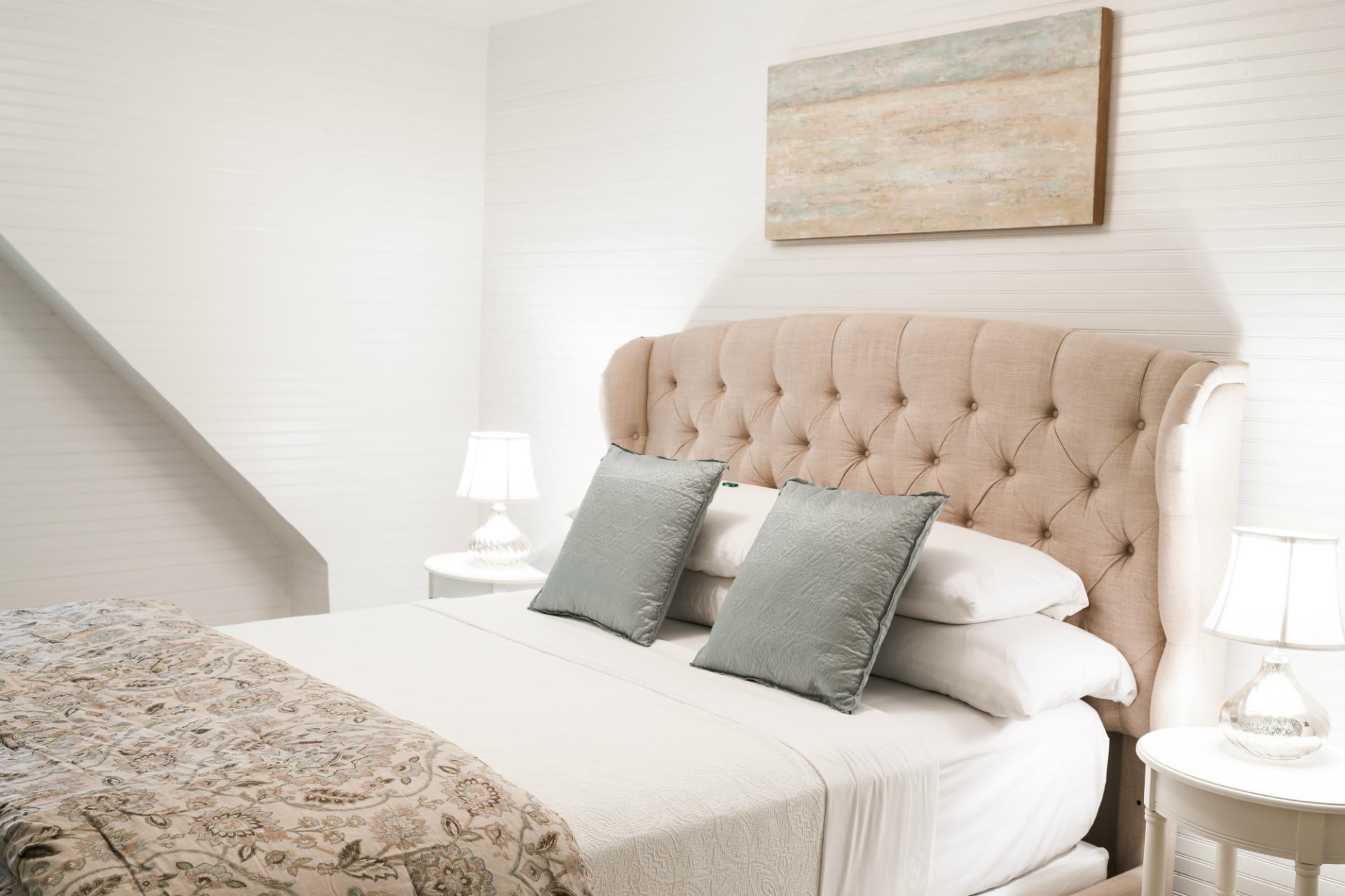 white oak inn suite bedroom with white linens