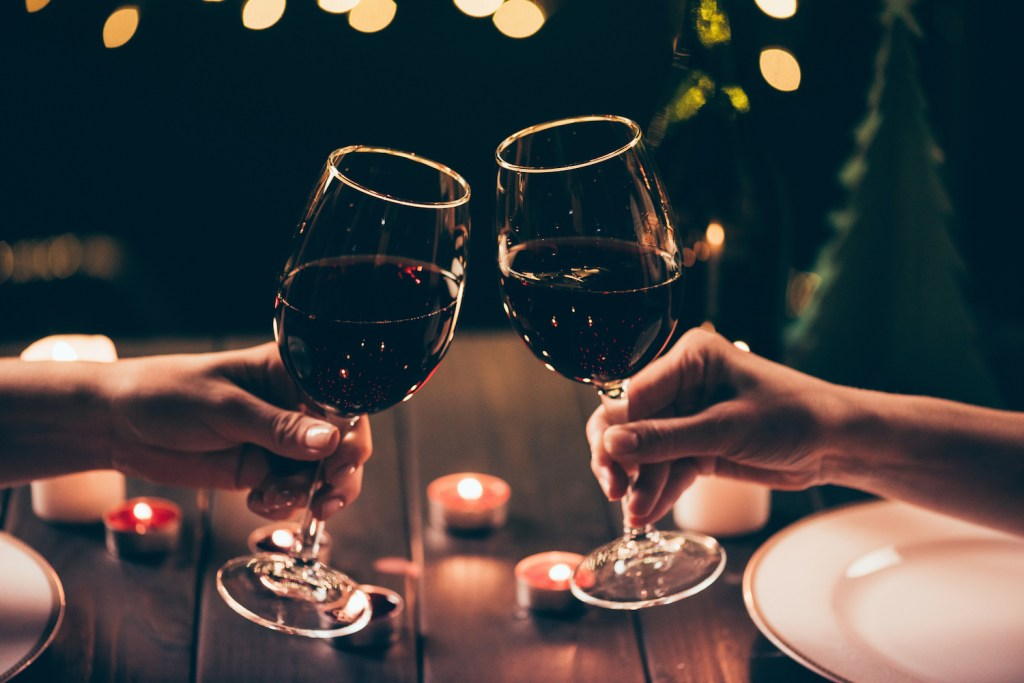 Cropped shot of two women clinking glasses with wine over served table with lit candles