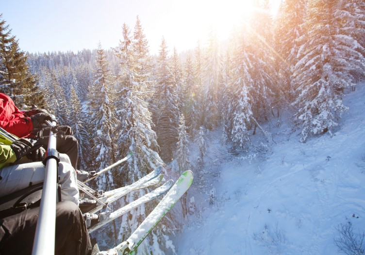 family sitting in ski lift skis danging over winter scene