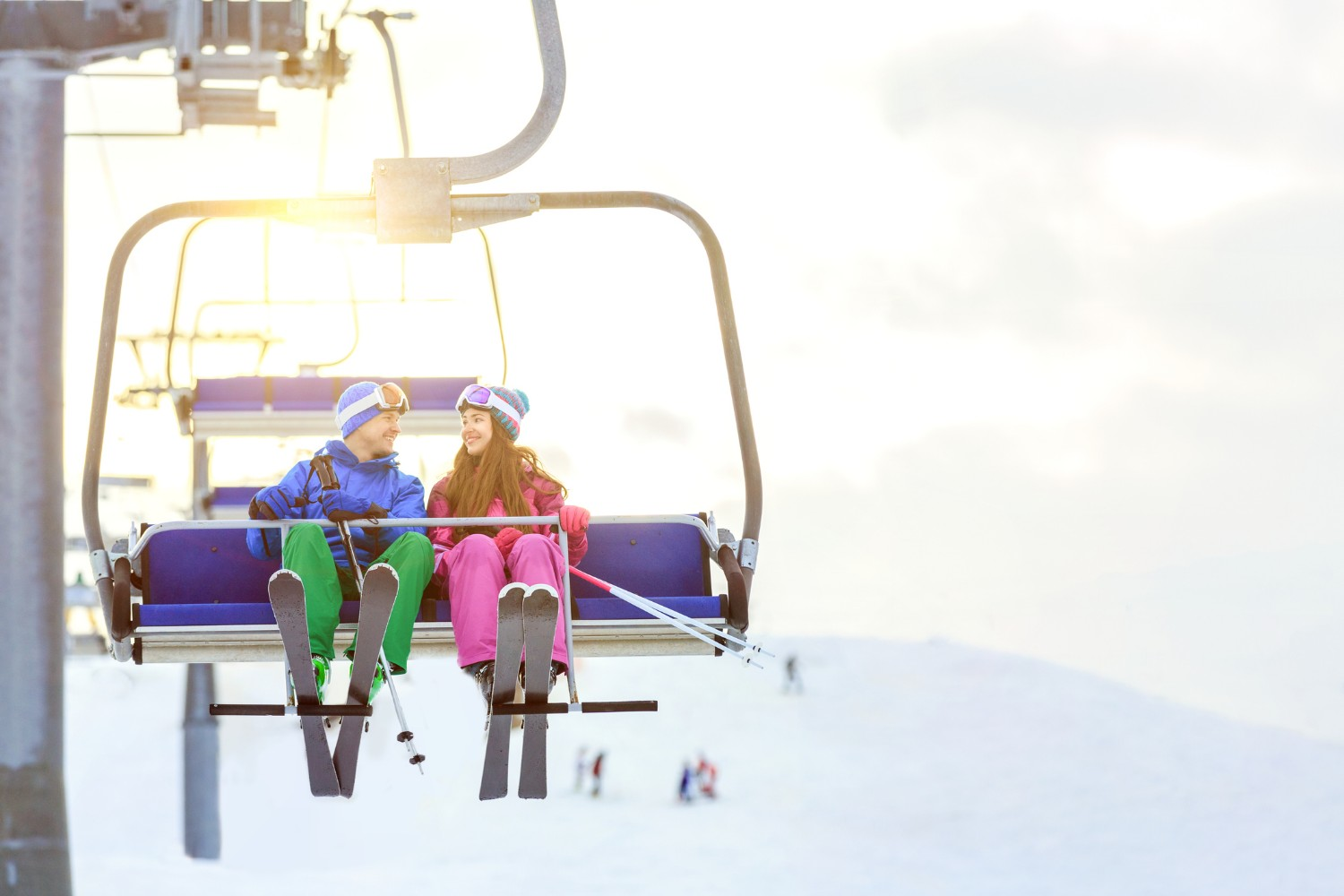 Young couple with skis outdoors on the ski lift