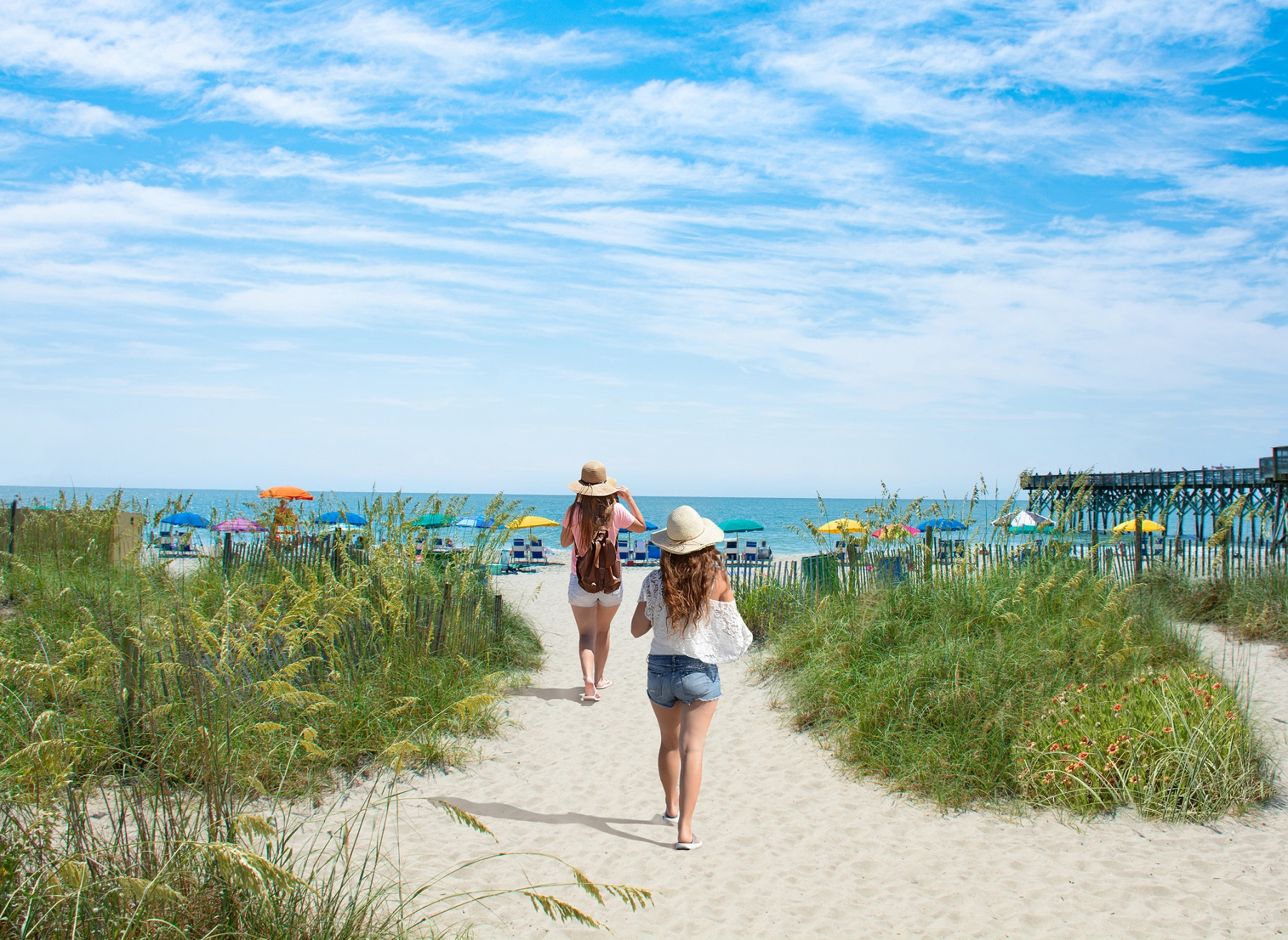 Girls waking on the beach. Footpath on sand dunes and ocean in the background. Myrtle Beach, South Carolina, USA