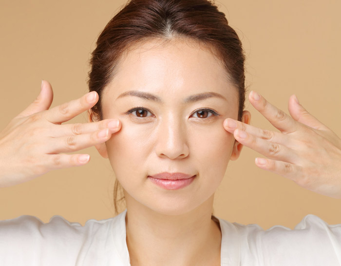 眼窩脂肪の解消のためにマッサージをする女性の画像