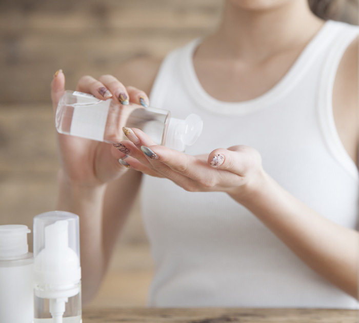 化粧水を手で付ける女性の画像