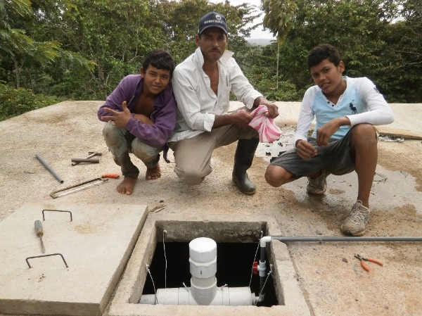 three Nicaraguan men kneel near their new water chlorination system