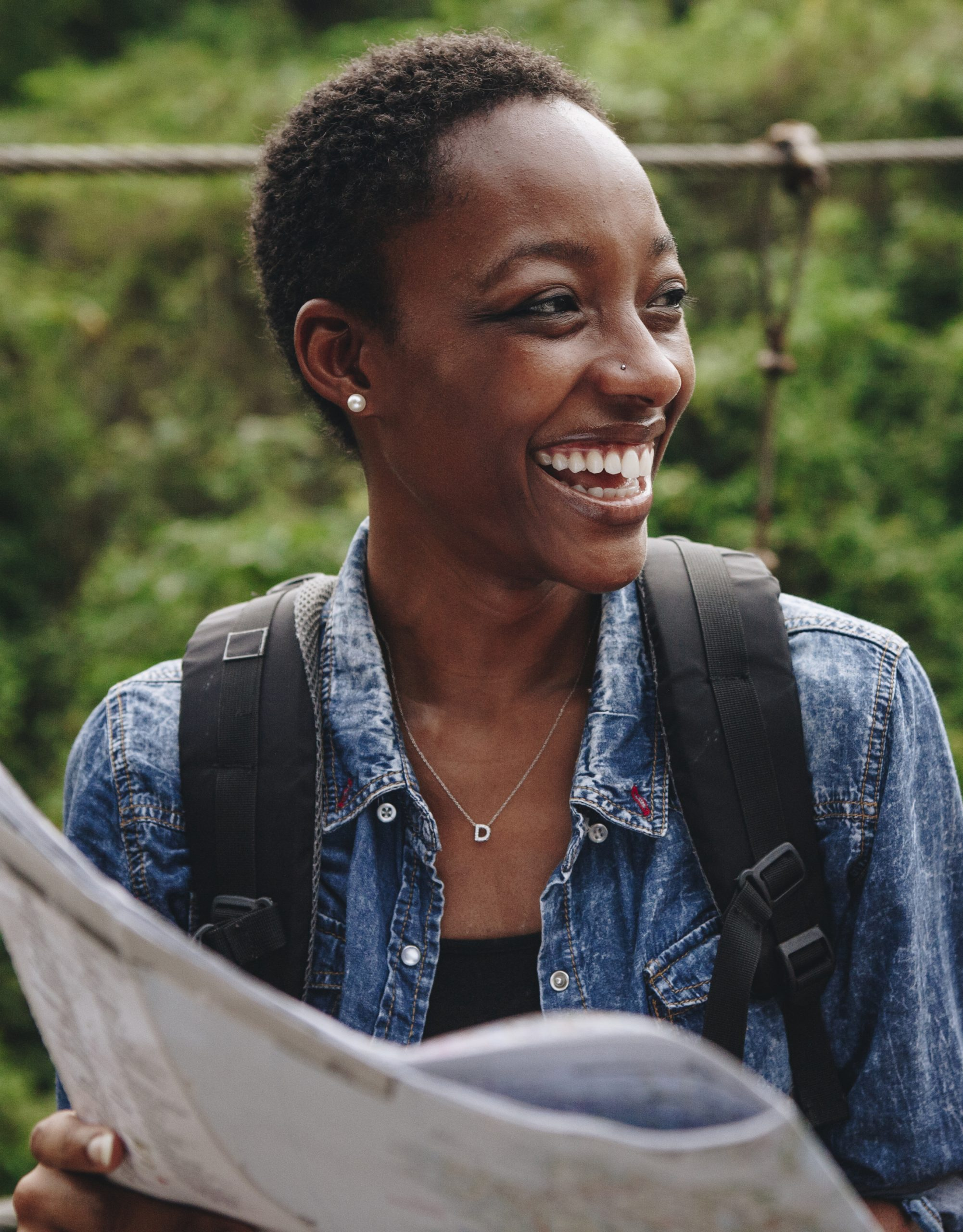Happy smiling black woman navigating with a map on SelfishMe Travel