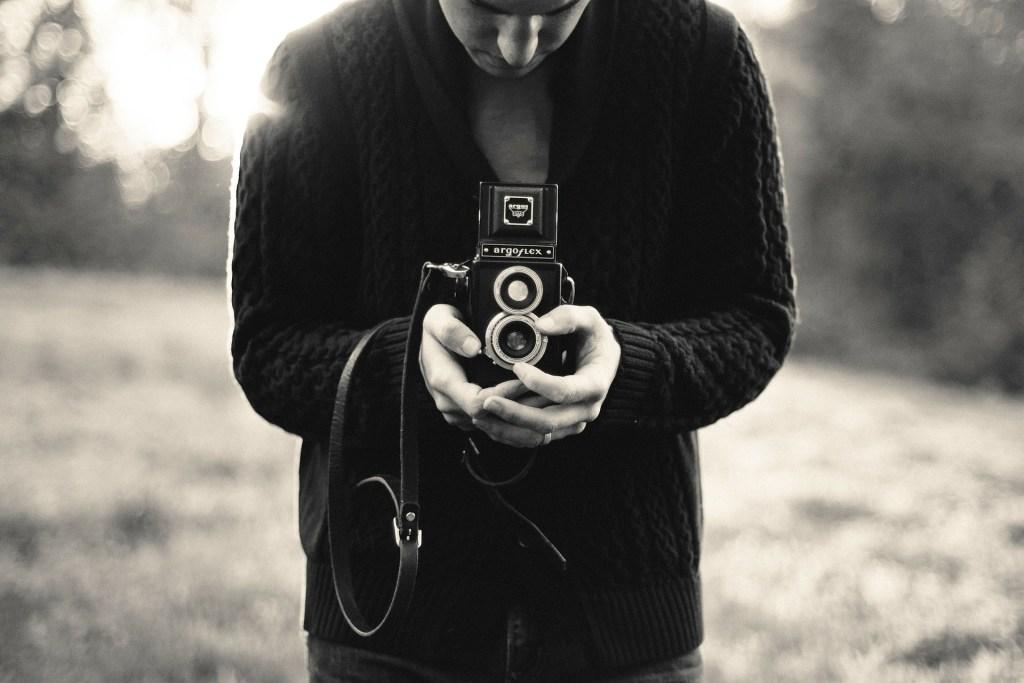 un appareil photo dans les bras d'un homme