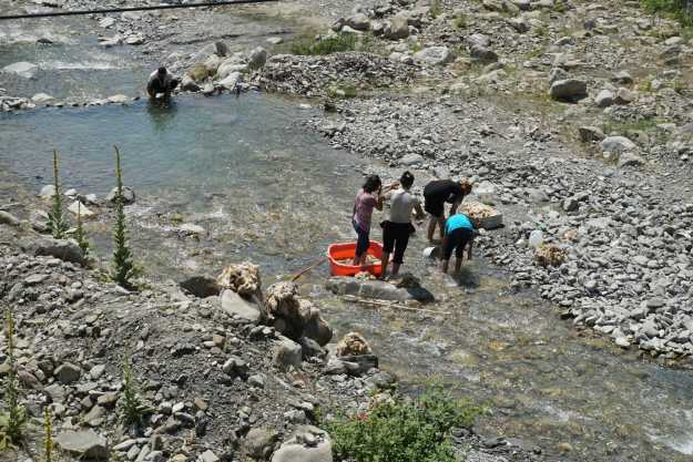 Kids washing fleeces & swimming in a river near Qax