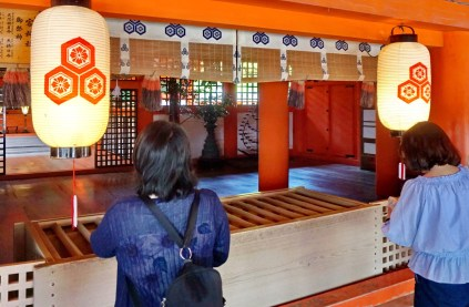 Devotions inside Itsukushima shrine.