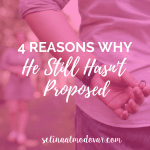 """man holding ring behind his back while facing a woman who stands in the distance with pink overlay and white text that reads, """"4 Reasons Why He Still Hasn't Proposed"""""""