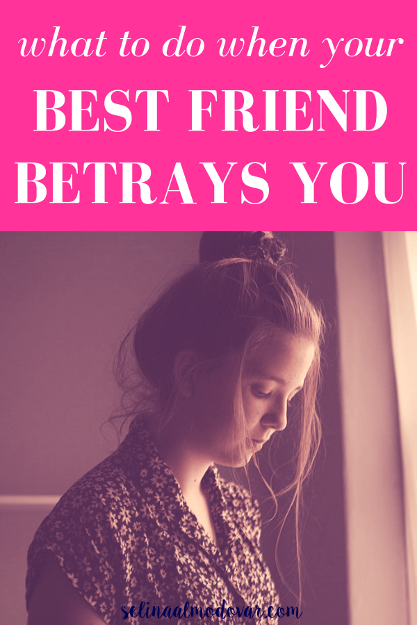 "sad girl wearing messy top bun is looking downward while standing next to a window with pink overlay and white text that reads, ""What To Do When Your Best Friend Betrays You"""