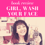 """Selina Almodovar smiling in front of bookshelf holding up the book, """"Girl, Wash Your Face"""" with pink overlay and white text that reads, """"Book Review: Girl, Wash Your Face"""""""