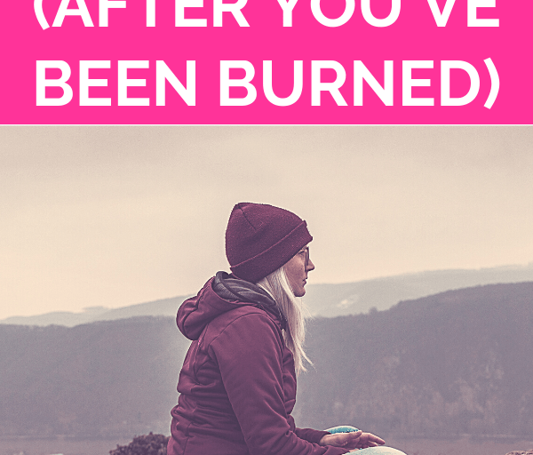 """blonde woman wearing a beanie hat sits facing the left, crossed-legged at an open mountain scenic location with pink overlay and white text that reads, """"Learning To Trust Again (After You've Been Burned)"""""""
