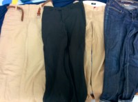 4 pairs of pants including a pair of jeans, a pair of cotton khakis, a pair of tan linen pants, and lightweight black pants.