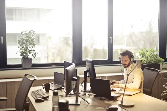 man with headphones looking at computer